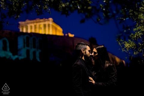 Foto's van een pre-huwelijksverjaardag van Athene van een paar kussen onder straatverlichting 's nachts | paar fotosessie