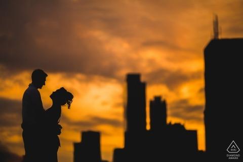 Photos de fiançailles de nuit d'un couple se profilant devant les bâtiments de la ville | Séance photo avant le mariage avec un photographe de DC