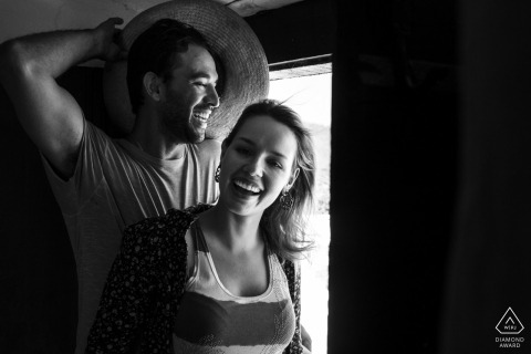black and white pre-wedding engagement pictures of a couple in a window | Rio de Janeiro portrait shoot