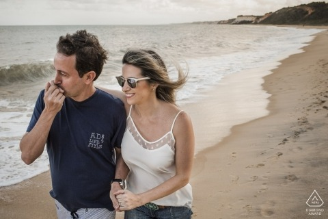 Brazil wedding photographer engagement portrait of a couple walking on the sandy beach  | Rio de Janeiro pre-wedding pictures
