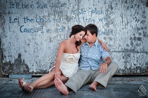 Florida engagement pictures of a couple sitting on concrete at the beach  | Key West photographer pre-wedding shoot with photographer