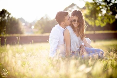 De verlovingfoto's van Toscanië van een paar die in het gras in de zon zitten Pistoia fotograaf pre-huwelijksportret sessie