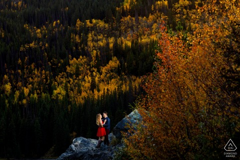 An adventerous couple enjoy the golden light and colorful Aspen trees near Frisco Colorado while celebrating their engagement