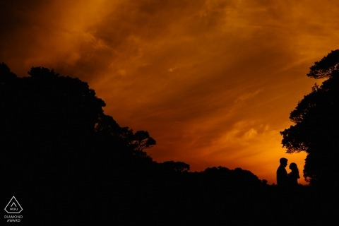 Brazil engagement pictures of a couple silhouetted with trees and orange sky with clouds  | Canion Fortaleza photographer pre-wedding photo shoot session