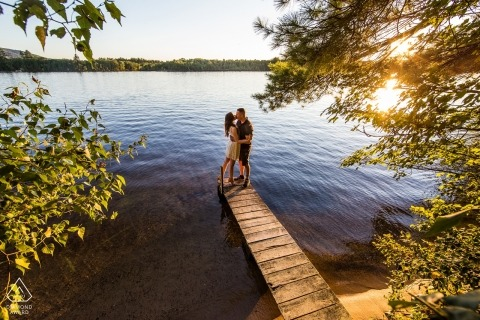 Engagement portrait of a beautiful sunset behind newly engaged couple on a dock in New Hampshire.