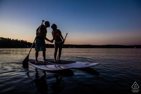 Verloofd paar op paddleboards uit op het water bij zonsondergang in Windham, NH.
