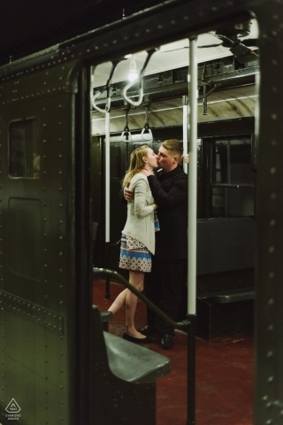 Une jeune femme et un homme s'embrassent à l'intérieur d'une ancienne voiture de métro de New York. Portrait de fiançailles au New York State Museum