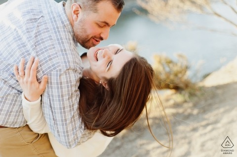 A young NY woman joyfully smiles as a young man dips her down in an embrace. Engagement Portrait by a New York Lake at Sunset