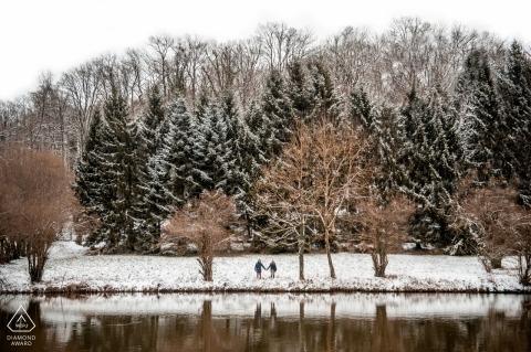 Verloofd paar dat in sneeuw met bomen en bergen loopt Séance engagement fotografie - Frankrijk