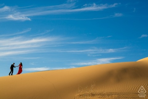 Couple walking through the Glamis Sand Dunes for a Desert Engagement Session