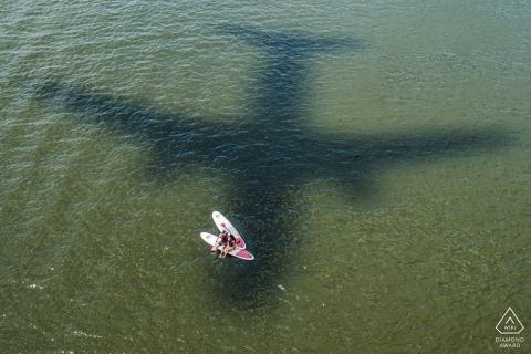 Photographie de fiançailles pour un mariage SUP dans le District de Columbia avec l'ombre d'un avion sur l'eau