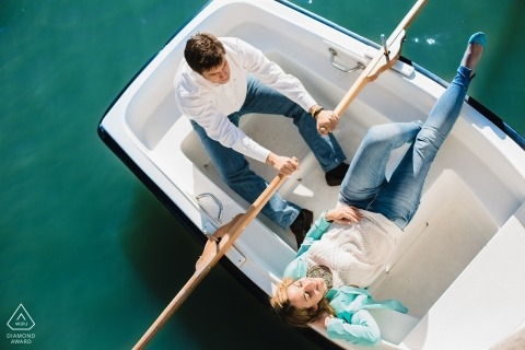 A Spain engaged couple pose in a row boat for their pre-wedding portraits for Madrid engagement photographer