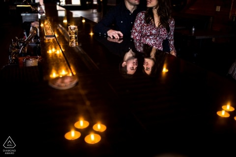 Reflection of couple in bar during their wedding engagement photo shoot in MN.