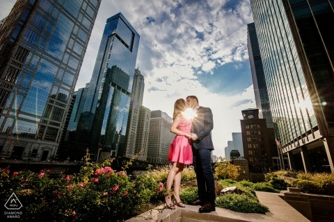 Chicago urban engagement portrait with tall buildings, sun and clouds.