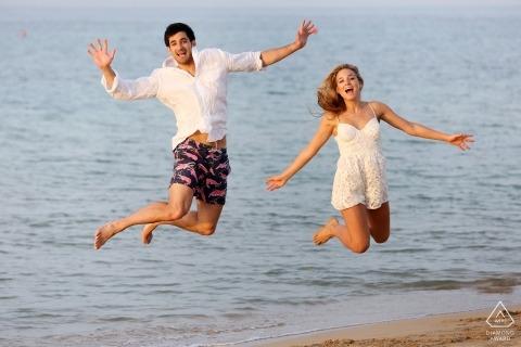 Sesión de fotografía previa a la boda de Bari con una pareja saltando por el agua en la playa