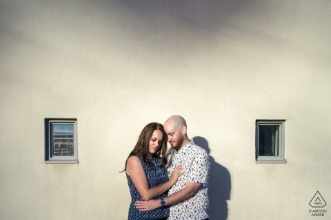 Ontario Engagement Photography of a couple against wall with the sun
