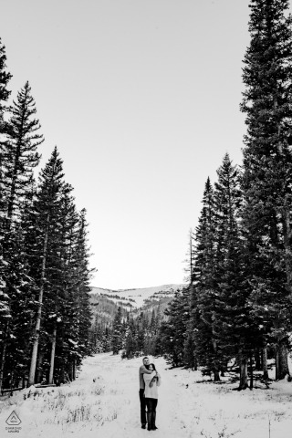 engagement photo of couple between trees and snow | Rocky Mountain National Park, Estes Park, Colorado | photo after first snow