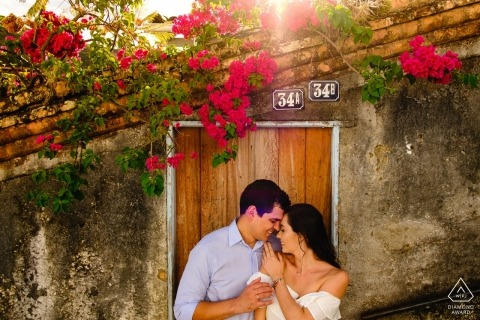 Minas Gerais Engagement Photo Session with a couple in the sun with buildings and flowers