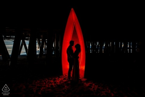 Rood silhouet onder de pier van Santa Monica | California Engagement Portrait Fotograaf
