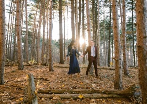 Portland, Maine Engagement Photography Session im Wald mit niedrigem Sonnenlicht und Bäumen