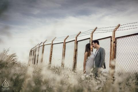 Amour devant le mur de fil - Photographie de fiançailles avec fil de fer barbelé surmonté de clôture