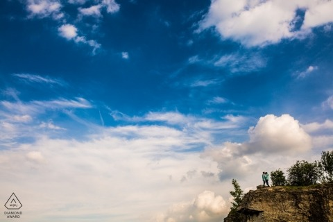 Brno Stránská skála engaged couple on a cliff overlooking a scenic filled with clouds and blue sky