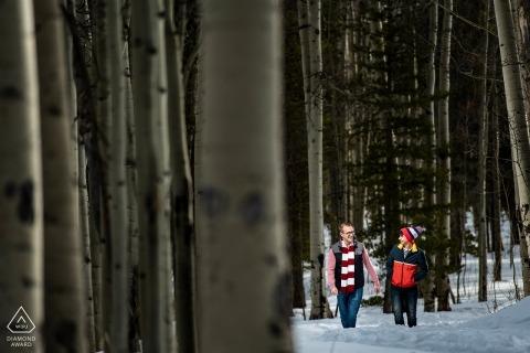 Séance d'engagement du Kenosha Pass | Photo de mariage dans le Colorado - Un marié et une mariée marchant à travers les trembles.