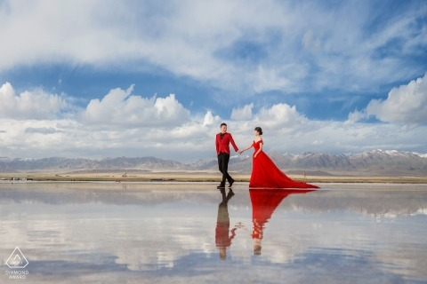And engaged Chinese couple walk on a clouded mirage for their pre-wedding portrait
