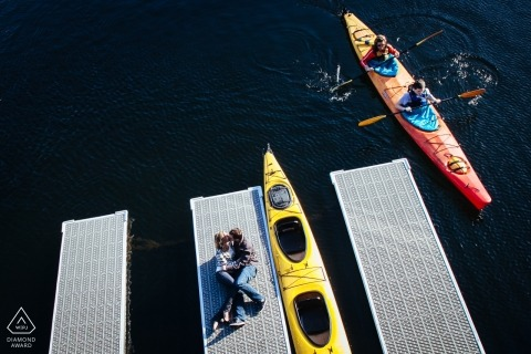 Engagement Session Puget Sound - Couple laying down kissing on dock in marina