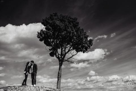 Sesión fotográfica del Engagament de la Toscana con árboles y nubes en blanco y negro