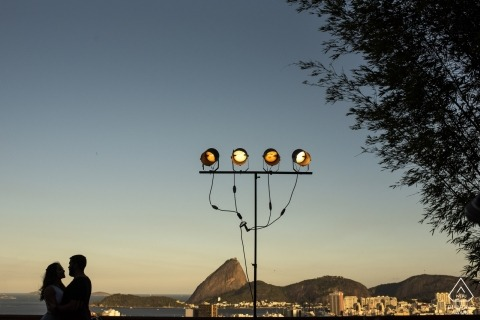Verlobte Paare sind silhouettiert, während sie die Aussicht auf Rio de Janeiro, Brasilien, von ihrer Aussichtstour genießen