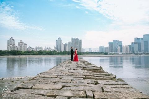Vor-Hochzeits-Verlobungs-Porträts Fujian China auf Stein-Anlegestelle mit Stadt und Wasser