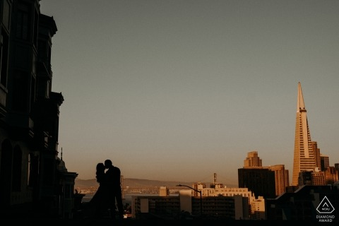 The San Francisco city skyline is behind this silhouetted kissing couple