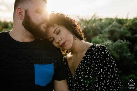 Rio de Janeiro couple embraced with her eyes closed in the warm afternoon sun for their pre-wedding portrait