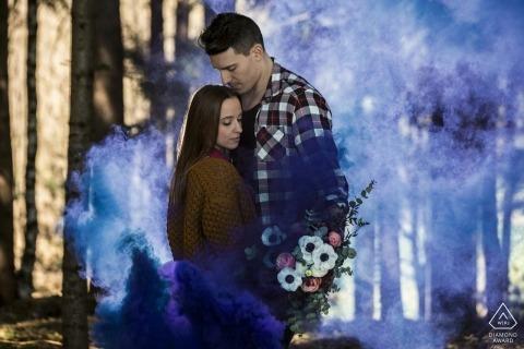 Niebieskie dymne włoskie zdjęcie zaręczynowe w lesie z bukietem kwiatów