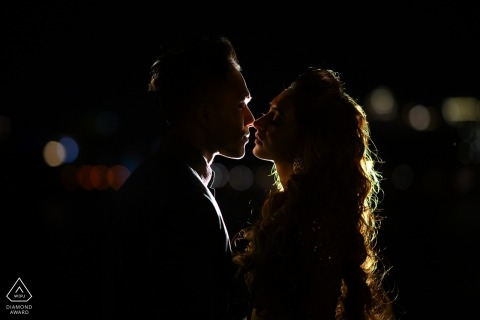 Udaipur, India pre-wedding profile portrait | back lit photo shoot at night of a couple about to kiss