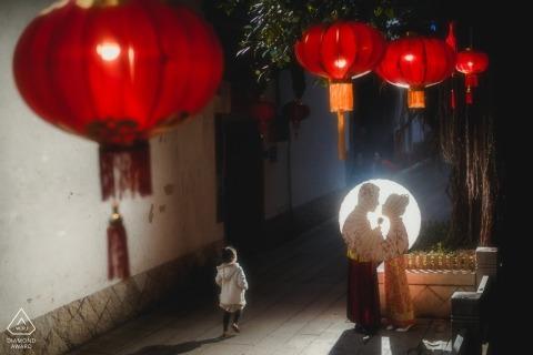 FUZHOU, CHINE session précédant le mariage - un couple s'embrassait derrière un parapluie pendant qu'un enfant courait.