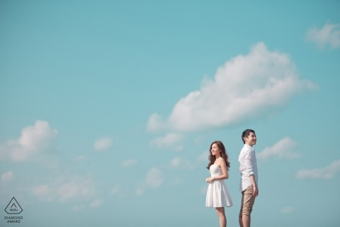 Jeju, Korea couple shooting pre-wedding portraits with a blue sky and clouds