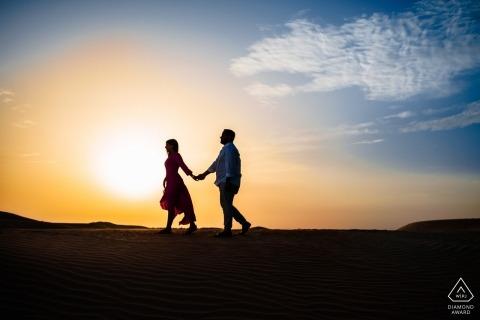 Paare, die in Wüstensonnenuntergang durch Dubai-Hochzeitsfotograf gehen