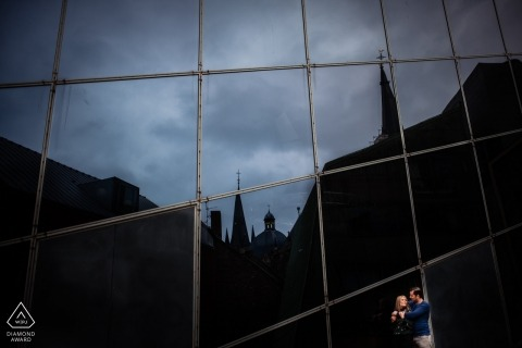 Engagement portraits from Aachen | a couple lit with the city silhouette behind them