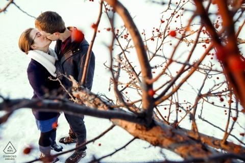 Tenney Park, Madison, Wisconsin pre-wedding portretten | Het verloofde paar neemt een moment om te kussen tijdens een wandeling op de besneeuwde golfbreker van het meer Mendota.