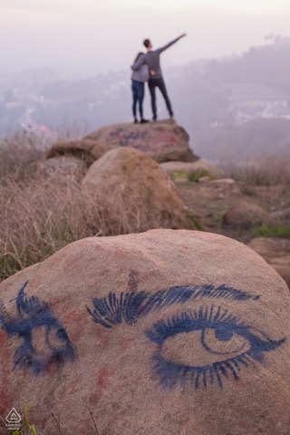 Hollywood, California engagement portraits in the hills | Photographer spots a drawing on the rock while the couple has fun on the other side.
