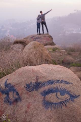 Portraits de fiançailles à Hollywood, Californie dans les collines | Le photographe repère un dessin sur le rocher pendant que le couple s'amuse de l'autre côté.