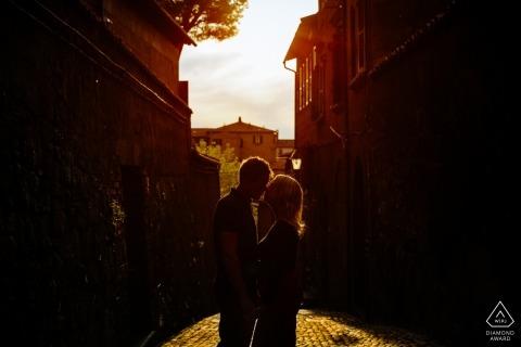 Symmetrical Orvieto Engagement portrait au soleil de fin d'après-midi avec un couple presque silhouetté entre les bâtiments