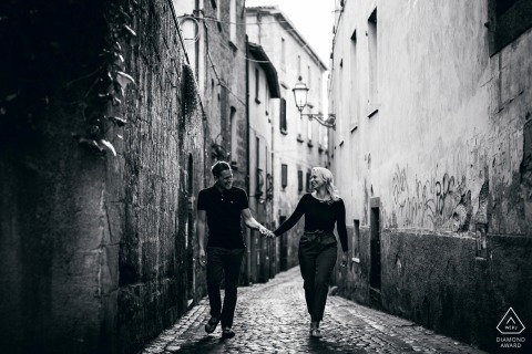 Orvieto Engagement Photos in black-and-white | the couple walks holding hands Down a narrow cobblestone street