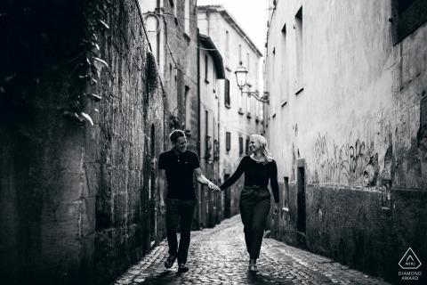 Orvieto Engagement Photos en noir et blanc | le couple se promène main dans la main dans une rue pavée étroite