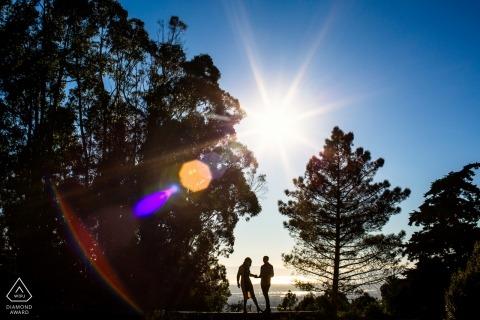 Retratos de compromiso de Oakland Hill | Cielos azules, rayos de sol, árboles y una pareja en silueta.