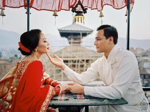 Photographie de film avant le mariage à Kathmandu, au Népal | une tendre touche son menton avec sa robe rouge