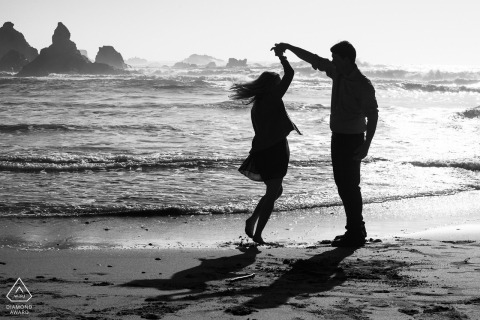 Jughandle State beach, Mendocino, CA portrait session - newly engaged couple dancing twirl on the beach