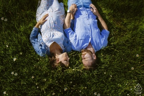 Engagement photo session of a couple laying down in a field in Aachen.